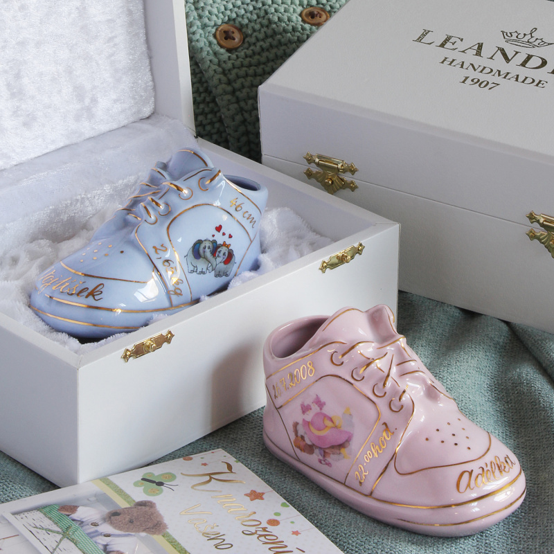 Small shoe on the occasion of child´s birth in gift packaging blue